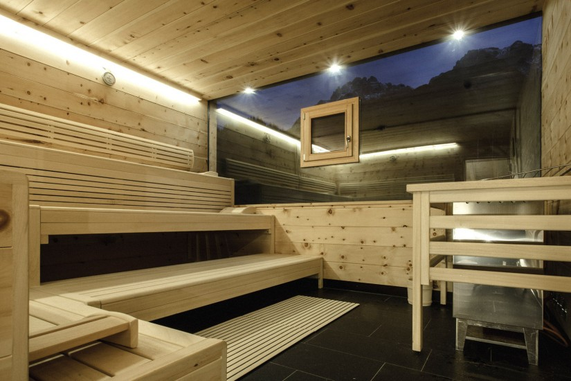 Eine Finnische Panorama-Sauna mit Steinberge-Blick, kühlender Felsenduschen und Frischluftraum wartet auf euch.
