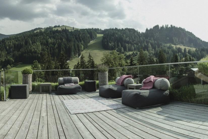 Am Dach sitzt man auf XXL-Sitzkissen und Liegestühlen und genießt in gechillter Atmosphäre den grandiosen Blick zu den Leoganger Steinbergen.